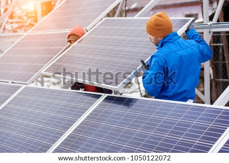 Technicians in blue suits mounting photovoltaic solar panels on roof of modern house. Solar modules as ecological renewable energy sources. Alternative production modules power sustainable resources