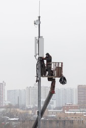 Technicians install mobile signal amplification devices on tower. It's nasty. Unrecognizable people. Technology concept, 5G, equipment improvement, professions, microwave danger, internet of things.