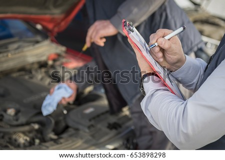 Technicians perform vehicle checkup and make notes for vehicle owner #653898298