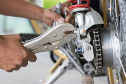 Technicians use locking pliers to unscrew screws to fix the motorcycle.