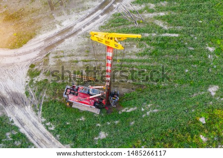 Technique a machine for driving piles of the foundation of a house into the ground at the beginning of construction, aerial view