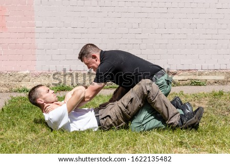 Technique of release from capture and strangulation in a prone position. Martial arts instructors demonstrate self-defense techniques of Krav Maga