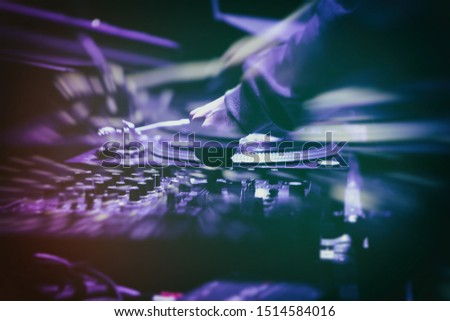 Techno party dj plays set on stage in nightclub.Professional disc jockey mixes musical tracks on concert.Double exposure & motion blur effects.Musician playing hip hop music on festival in the club