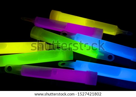 techno party gear and nightclub conceptual idea with vibrant color glow sticks in blue, green, purple and yellow glowing in the dark
