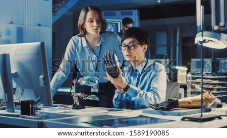 Technological Prosthetic Robot Arm is Closely Tested by Two Professional Specialists in a High Tech Research Laboratory with Modern Futuristic Equipment. Man and Female Talk and Ananlyse the Object.