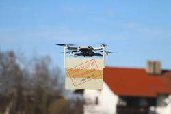 Technological shipment concept during pandemic coronavirus, drone fast delivery, multicopter flying with cardboard box to deliver chloroquine to a private house in the background (purposely blurred)