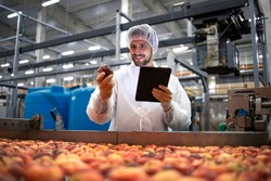 Technologist doing quality control of apple fruit production in food processing plant.