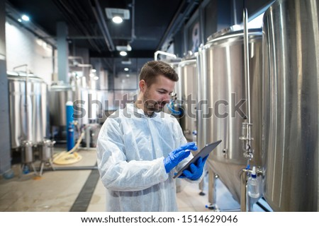 Technologist expert using tablet computer in food factory production line. Factory worker controlling production.