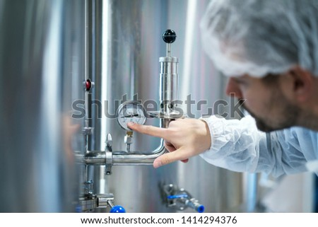 Technologist in white protective suit checking pressure on pressure gauge on industrial machine in factory.