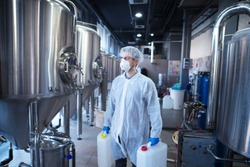 Technologist industrial worker holding plastic canisters about to change chemicals in the food processing machine. Cleaning in food factory.