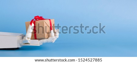 Technology and consumerism. Gift box in automated robot hand, blue panorama background