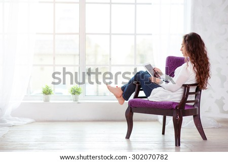 Technology and coziness. Beautiful young woman using tablet computer while sitting at armchair at home.
