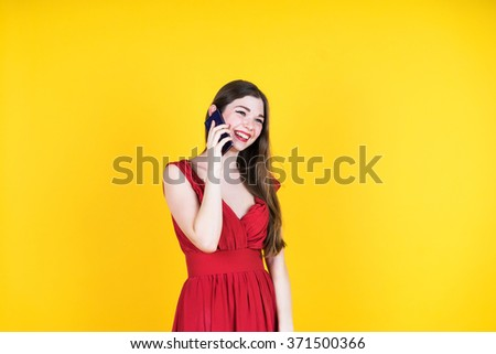 Technology  and leirure concept -  smiling young woman talking with smartphone . Isolated studio, yellow background, female model. - Shutterstock ID 371500366
