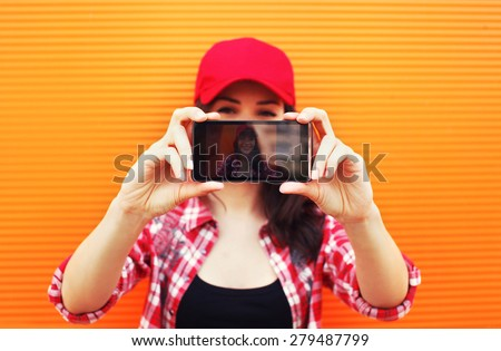 Technology and people concept - pretty girl makes self-portrait on the smartphone outdoors against colorful wall