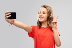 technology and people concept - smiling young woman or teenage girl in blank red t-shirt taking selfie by smartphone over grey background