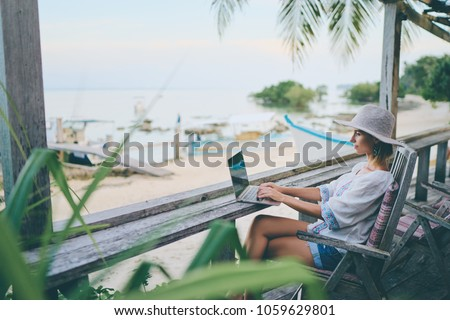 Technology and travel. Working outdoors. Freelance concept. Pretty young woman using laptop in cafe on tropical beach.