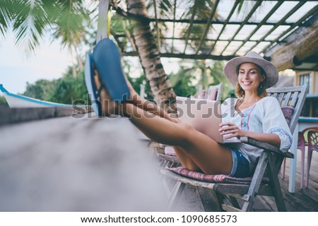 Technology and travel. Working outdoors. Freelance concept. Pretty young woman using laptop in cafe on tropical beach. #1090685573