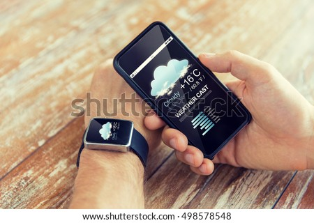 technology, application, weather forecast and people concept - close up of male hand holding smart phone and wearing watch with cloud icon and air temperature on screen