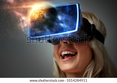technology, augmented reality and people concept - happy young woman with virtual headset or 3d glasses over planet and space background #1014284911