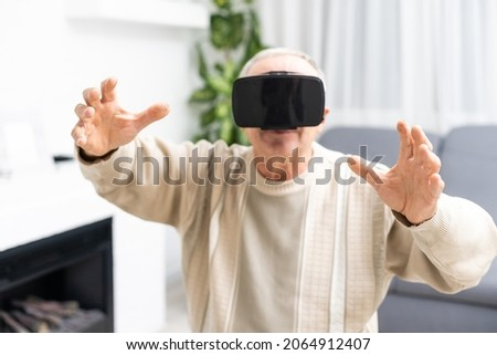 technology, augmented reality, gaming, entertainment and people concept - senior man with virtual headset or 3d glasses playing videogame at home.