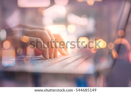 Technology business and working concept. Close up woman hand using keyboard and notebook double exposure blur people bokeh light background. Shallow depth of field. Vintage tone filter color style.