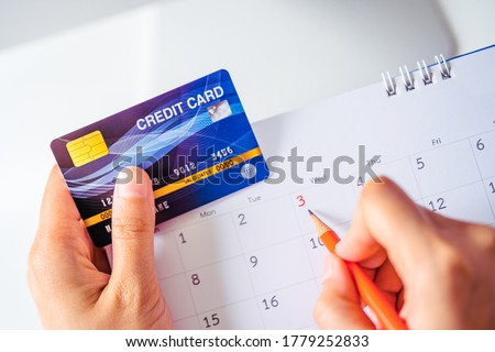 Technology business concoept: One hand hold a Credit card while other hold orange pencil pointing the date on calendar for checking and planning of billing due date or maturity date