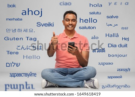 technology, communication and people concept - happy indian man with smartphone showing thumbs up sitting on floor over greeting words in different foreign languages on grey background ストックフォト ©