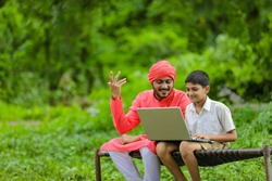 Technology concept : Indian farmer child using laptop