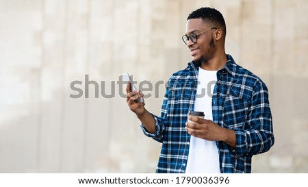 Technology Concept. Young successful afro designer reading good news from friends on phone and enjoying morning coffee