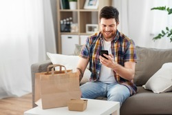 technology, consumption and people concept - smiling man using smartphone for food delivery at home