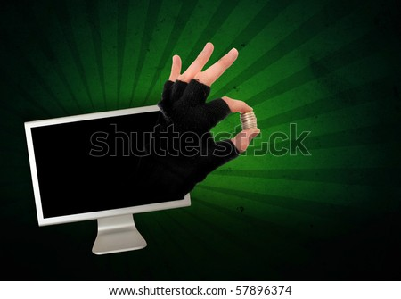Technology crime. Hand in glove is reaching out from the computer monitor to take your money away, abstract image.
