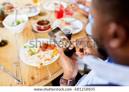 technology, eating and people concept - hands with smartphone photographing food at restaurant