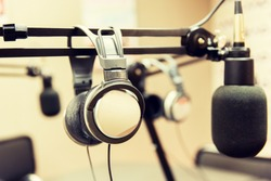 technology, electronics and audio equipment concept - close up of headphones and microphone at recording studio or radio station