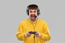 technology, gaming and people concept - angry young man or gamer in headphones with gamepad playing and streaming video game over grey background