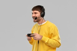 technology, gaming and people concept - happy smiling young man or gamer in headphones with gamepad playing and streaming video game over grey background