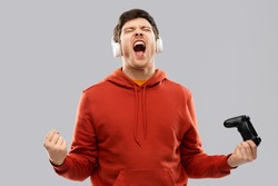 technology, gaming and people concept - happy young man or gamer in headphones with gamepad winning in video game