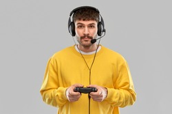 technology, gaming and people concept - young man or gamer in headphones with gamepad playing and streaming video game over grey background