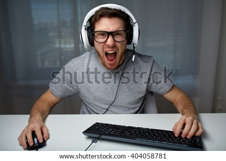 technology, gaming, entertainment, let\'s play and people concept - angry screaming young man in headset with pc computer playing game at home and streaming playthrough or walkthrough video