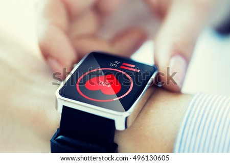 technology, health care and people concept - close up of woman hands checking pulse by smartwatch with heart icon on screen