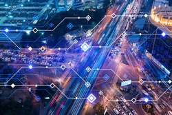 Technology hologram on aerial view of road, busy urban traffic highway at night. Junction network of transportation infrastructure. The concept of developing high-tech science in logistics.