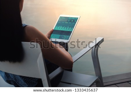 Technology in Finance and Business Marketing Concept. Graphs and Charts show on Touch Pad's Screen. Modern Woman seeing Statistical Data on Digital Tablet. Working via Internet while Vacation