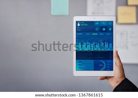 Technology in Finance and Business Marketing Concept. Graphs and Charts show on Touch Pad's Screen. Modern Businessman seeing Statistical Data on Digital Tablet in Office Meeting Room.