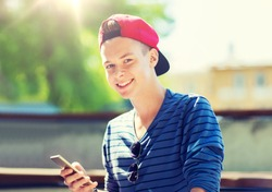 technology, internet and people concept - happy teenage boy with smartphone outdoors