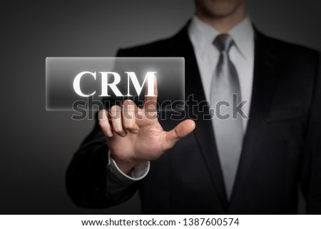 technology, internet, network, business concept - businessman in suit presses virtual touchscreen interface button - english word CRM