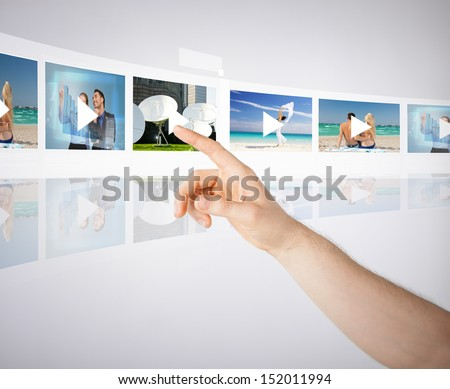 technology, internet, tv and virtual screens concept - man pressing button on virtual screen with videos