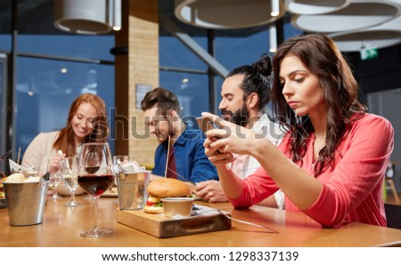 technology, lifestyle and people concept - bored woman dining with friends and messaging on smartphone at restaurant #1298337139