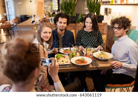 technology, lifestyle and people concept - happy friends with smartphone having dinner and photographing at restaurant #643061119