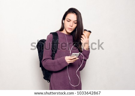 technology, lifestyle, internet addiction and people concept - Young beautiful woman with smart phone. Happy and smiling attractive woman looking at the mobile phone. Grey wall at the background. #1033642867