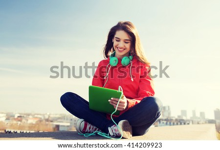 technology, lifestyle, music and people concept - smiling young woman or teenage girl with tablet pc computer and headphones outdoors