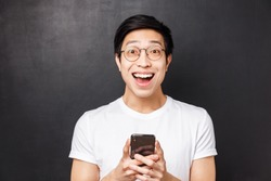 Technology, messaging and people concept. Close-up portrait of excited and amused happy asian man, smiling astonished and pleased, received positive reply in mobile phone messanger, hold mobile